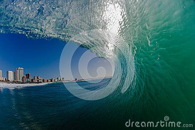 Photo picture image from inside a large clean  curling hollow wave. Looking out the wave as its crashing or pitching towards the shallows with a visual of Durban known as surf city. Water photography with a camera water housing and wide angle lens swimming into the wave.