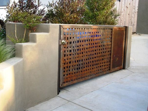 But not every trash enclosure needs to make a quiet statement. The woven metal door on this example, by Debora Carl Landscape Design, is something of a sculptural element in the yard.