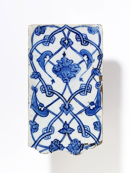 Tile of fritware, rectangular, painted in underglaze blue on a white ground with interlacing bands and leafy stems, symmetrically arranged. Iznik, Turkey, early 16th century