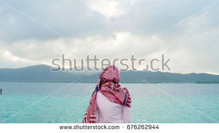 a women from behind enjoy morning at the beach