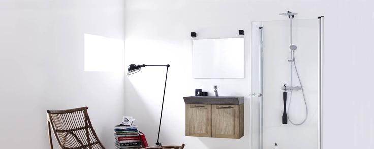 Een zuivere en natuurlijke uitstraling met deuren in eikenfineer en de rustieke, grijze betonnen wasbak. Maak ruimte voor een makkelijke stoel die tevens functioneert als mooi detail in de ruimte.
