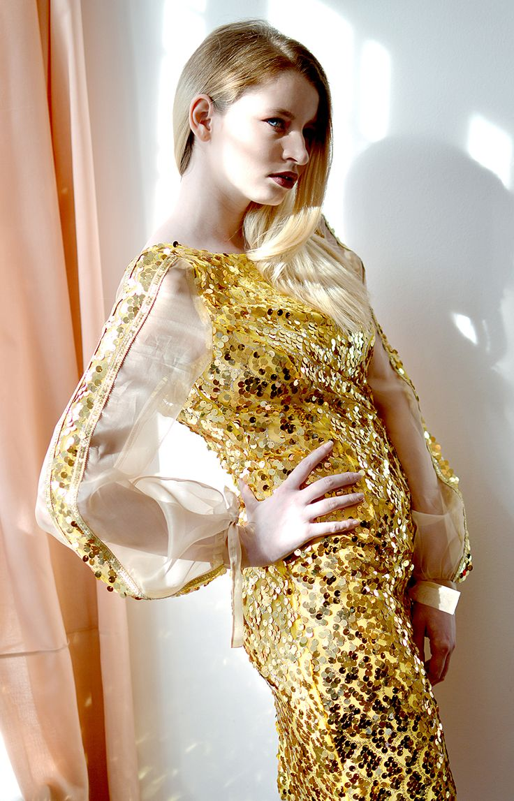 SOL is a yellow golden sequin tight dress with nude silk organza voluminous sleeves. The back is open and the dress closes with an invisible zipper.