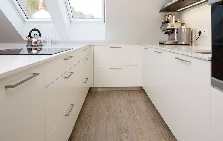 Clean white kitchen with stainless steel cabinet pulls by Hans Krug