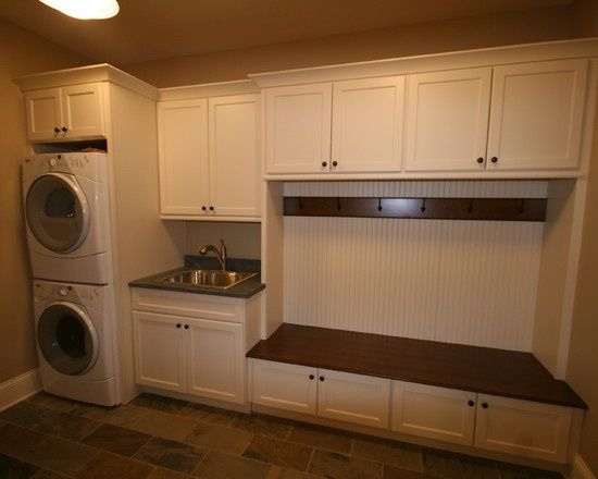 Stacked washer & dryer with bench, coat hooks, & cabinets in the mudroom.