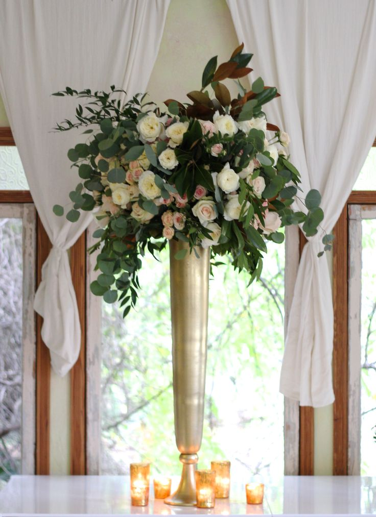 The altar arrangements will be tall gold vases with naturally shaped, lush white hydrangeas, green hanging amaranthus, blush roses, ivory garden roses, Italian ruscus, seeded eucalyptus, bay laurel, magnolia leaves, jasmine vine, ivory waxflowers, and Queen Ann's lace. www.stemfloral.com