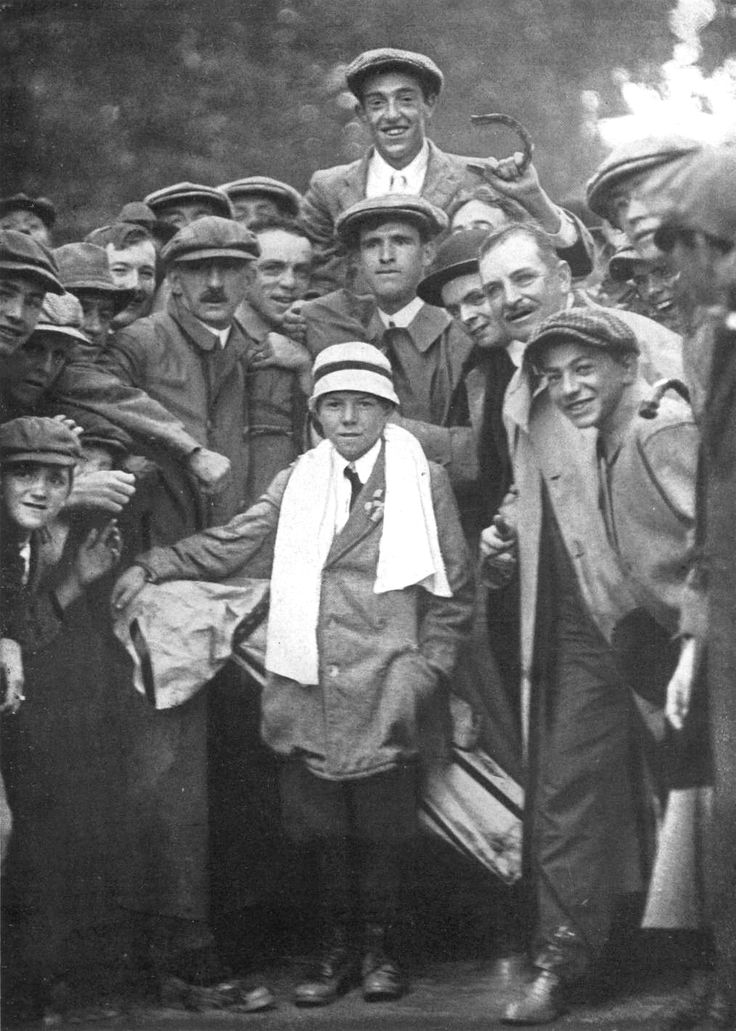 "Francis Ouimet being carried by spectators following his famous 1913 U.S. Open win holding a horseshoe. Eddie Lowery, the 10-year-old boy who was his caddie for the match, is in the foreground with a towel around his neck. The original caption read: ""Good Luck! Francis Ouimet on the shoulders of the crowd just after winning the Open Championship"""