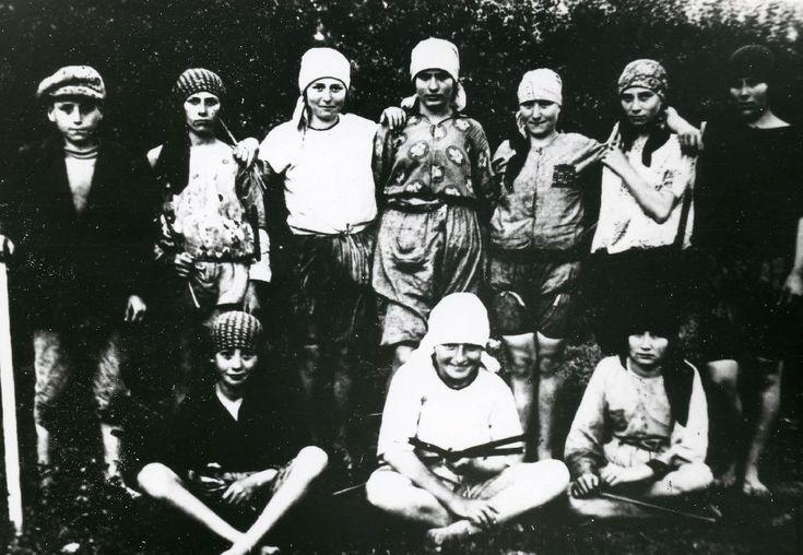 """Un gruppo di lavoro formato da giovani ragazze guidate dal """"sostituto caporale"""" il ragazzo con il bastone; nella fotografia compaiono Gombi Andreina e Albina (al centro in piedi e accovacciata con la camicetta bianca), sorelle del partigiano L"""
