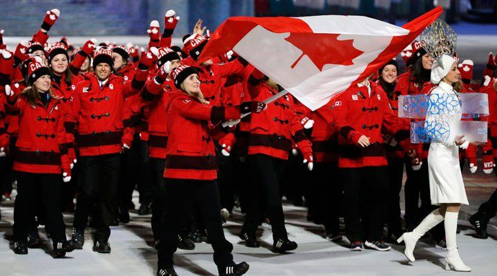 Hayley Wickenheiser of Canada carries the national flag as she leads the team during the opening ceremony of the 2014 Winter Olympics in Soc...