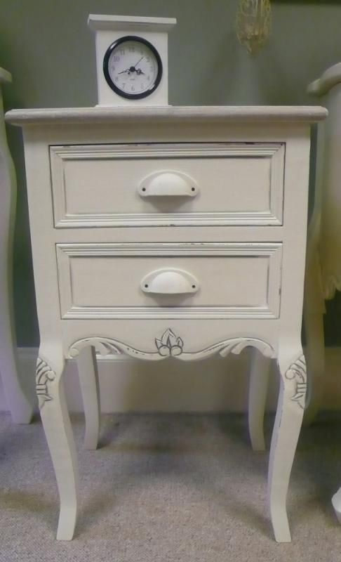 Cream bedside table - Country ash range. This two drawer bedside table also features ornate detailing and epitomises french country style   Measures 66cm high x 41cm wide x 33cm deep.  109.95 pounds
