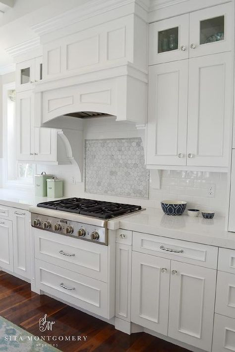 Beautiful kitchen features white cabinets paired with white quartz countertops and a white subway tiled backsplash.