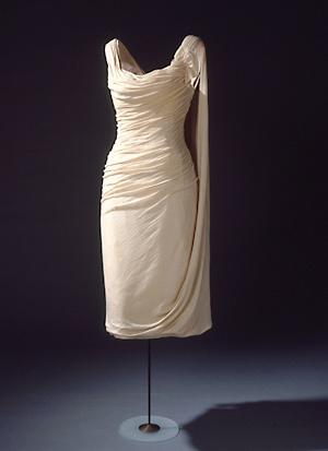 Kort aftenkjole fra Holger Blom i tynd, hvid uldjersey draperet på et foer. 1950'erne (Nationalmuseet)