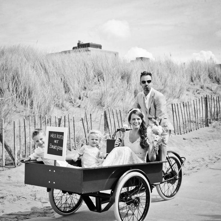 Een originele binnenkomer op jullie bruiloft: al fietsend rijdt de bruidegom zijn aanstaande het strand op.