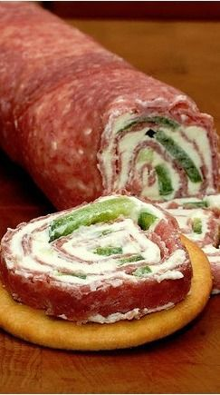 Salami and Cream Cheese Roll-Ups - quick, easy and excellent! Place a layer of plastic wrap on a metal sheet, cover with thinly sliced salami, spread softened cream cheese on salami, then peppers (optional). Roll up, wrap in fresh plastic and chill thoroughly before slicing. This is a perfect make-ahead party food - Cocina Adicto