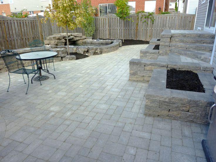 Backyard patio and stone wall backyard water feature for Interlocking brick house plans