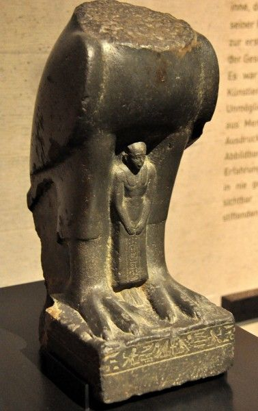 In this greywacke statue, the god Horus (depicted as a falcon; head is lost) protects the praying figure of Nectanebo II. From Memphis, Egypt. 30th Dynasty, circa 350 BCE. (State Museum of Egyptian Art, Munich, Germany).