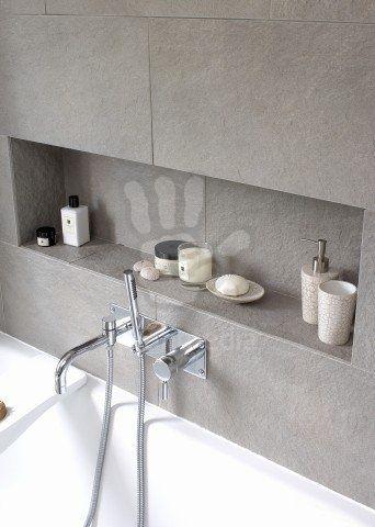 Recessed shelving above bathtub in modern bathroom