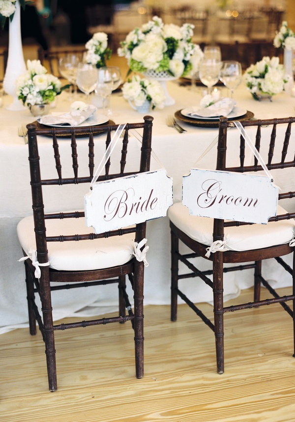 Vintage feel Bride & Groom signs, crisp white linens, and dark wood chairs. Lovely, rustic, and chic. #pinBellaFigura