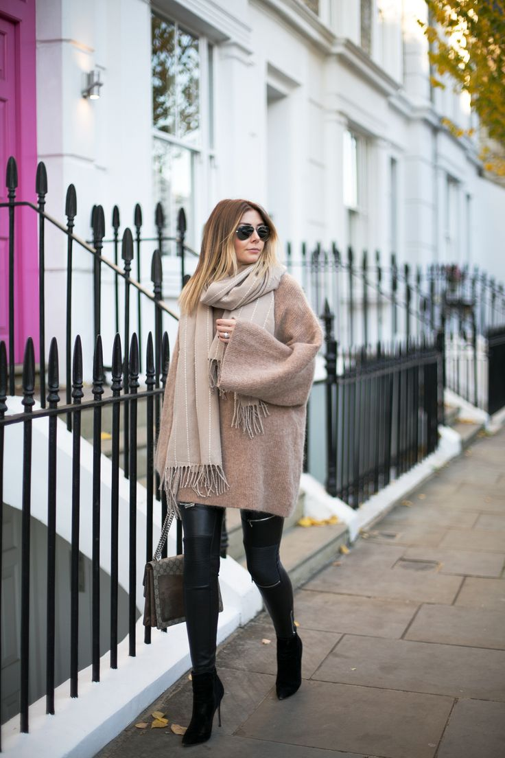Emma Hill wears camel mohair wide sleeve oversized jumper dress, leather zip biker trousers leggings, oversized camel scarf, heeled black ankle boots, cosy chic winter outfit