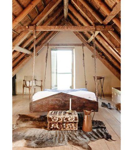 De estilo rústico, este quarto rústico aproveitou as vigas de madeira aparente para pendurar as correntes metálicas que sustentam a cama.