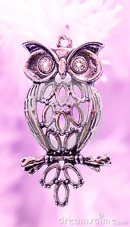 A closeup of a silvery owl ornament with sparkling diamond eyes.