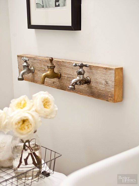 Rustic bathroom decor should look as if it has been handled by many people over a long period of time. This room-appropriate artwork features three vintage faucets that double as towel hooks when needed.