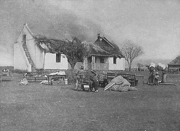 Australia doing battle during Anglo-Boer war at Rensburg A Boer family with a few belongings they were allowed to save, watch as their home is burnt down by  the English. Behind the women one can see one of the English soldiers on a horse.