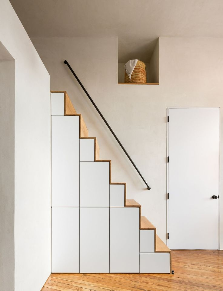 A custom storage staircase leads to the sleeping loft. The door to the half bath is on the right.