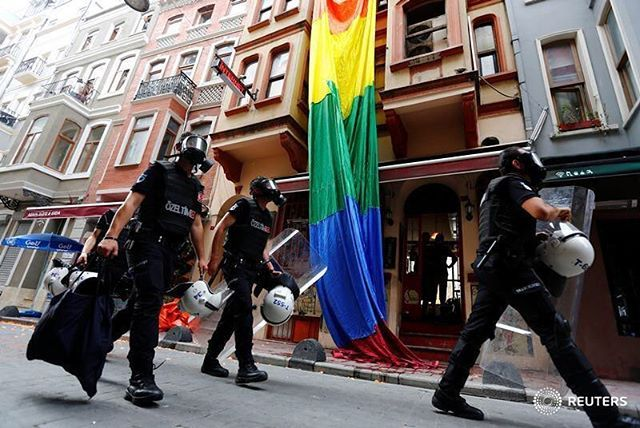 Riot police, with a rainbow flag in the background, chase LGBT rights activists as they try to gather for a pride parade, which was banned by the governorship, in Istanbul, Turkey, June 26, 2016. REUTERS/Murad Sezer @muradsezer #reutersphotos #lgbt #turkey #istanbul #gaypride