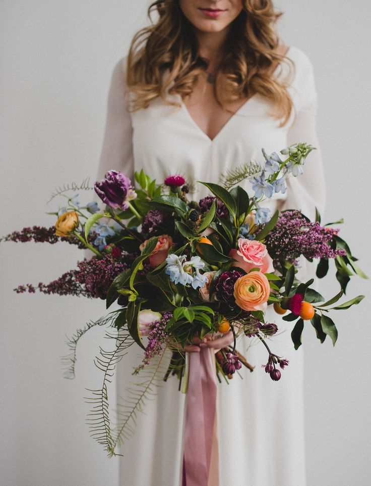 Purple bouquet with subtle pops of orange + blue