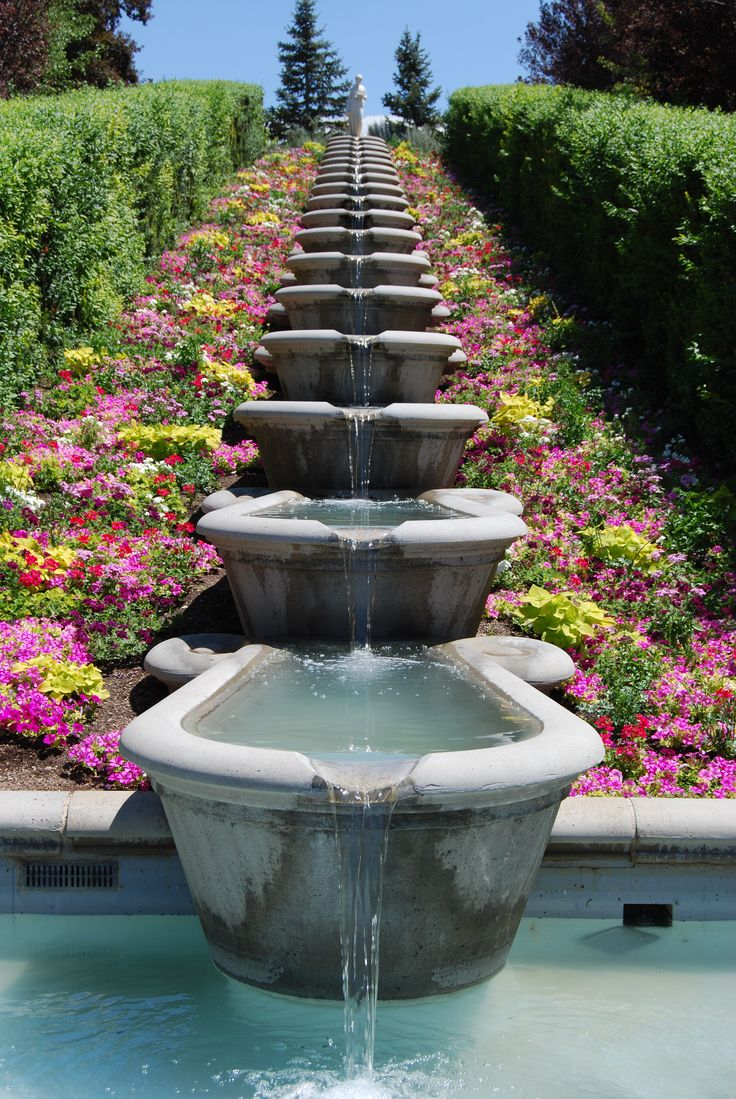 multi tiered fountain with gorgeous flower garden