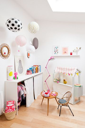 Cute kids play area/ clothing storage with white walls and bright accents.