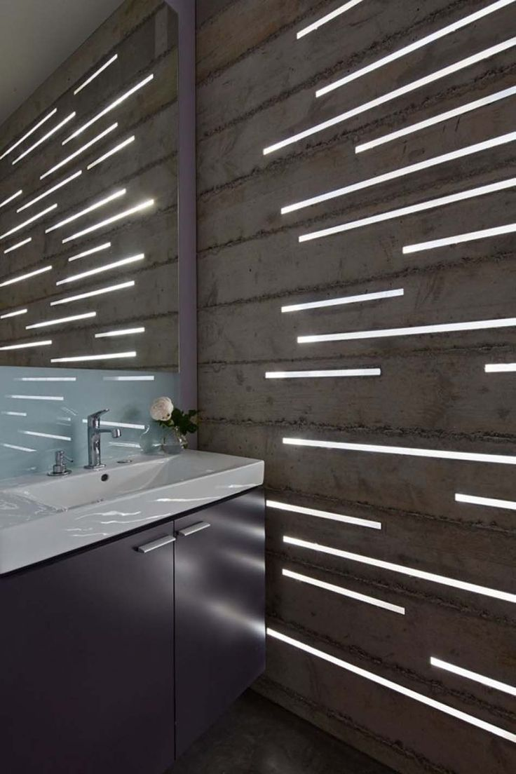 Luminaires LED intégrés dans un mur en béton brut garantissent une ambiance originale
