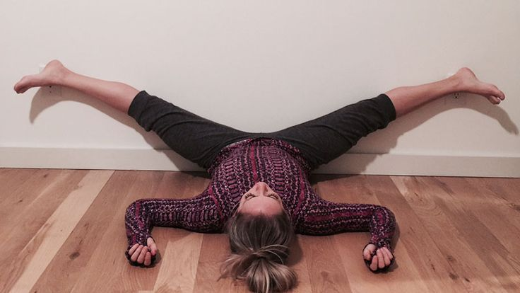Wall Restorative Yoga Poses- When just gathering the props for restorative yoga sounds exhausting, Kathryn Budig's fuzzy-slipper-friendly wall recharge session saves the day.