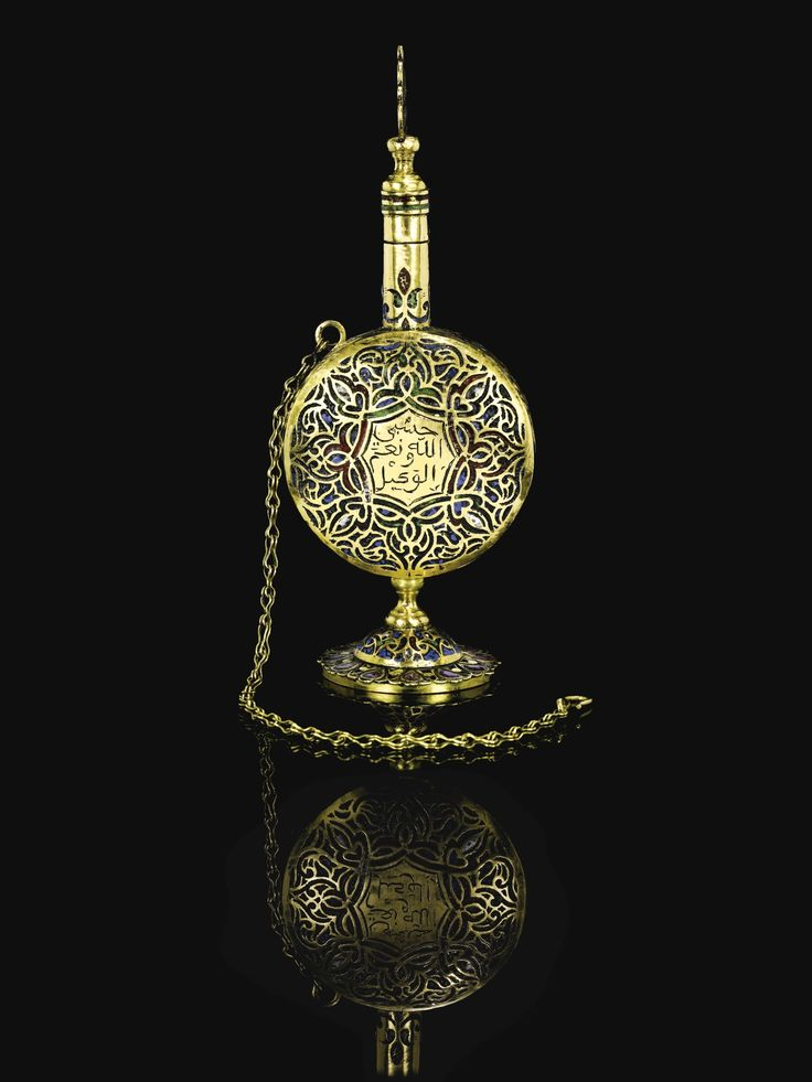 An Enamelled Gold Kohl Bottle, Morocco, Circa 18th Century the round body decorated in a multi-coloured enamel geometric pattern featuring an inscription to the centre to one side, on a short stand set with drop-shaped pink gemstones, the thin elongated neck containing a kohl stick with an enamelled handle and gold chain hooked to body for attaching Quantity: 2 16cm. height.