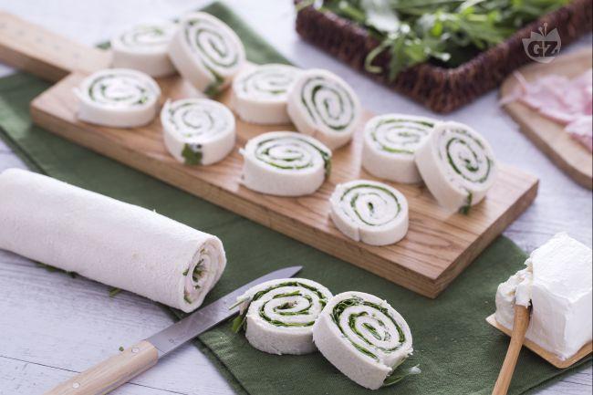 Le girelle al prosciutto cotto e rucola sono stuzzichini formati da pancarrè spalmati con  crema al prosciutto e rucola, arrotolate e poi affettate.