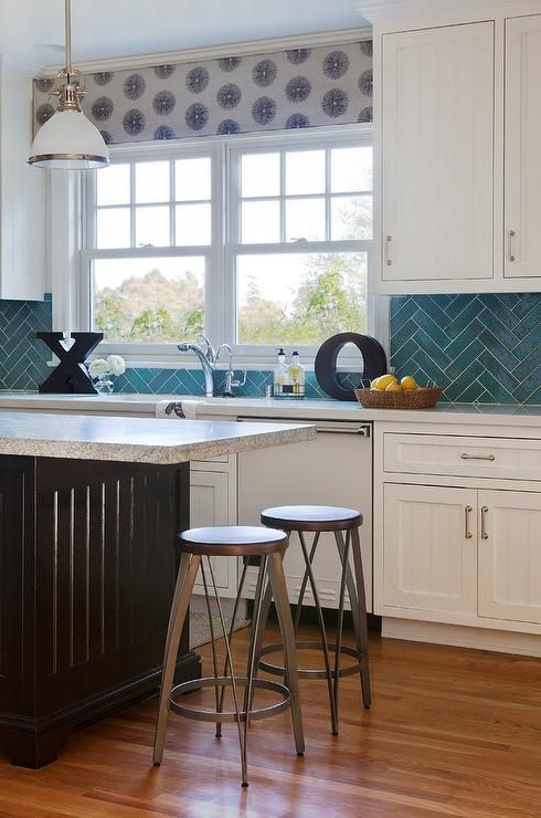 Lovely kitchen with white beadboard cabinets paired with white countertops and a turquoise herringbone tile backsplash.