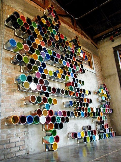 brick wall decorated with empty paint pails