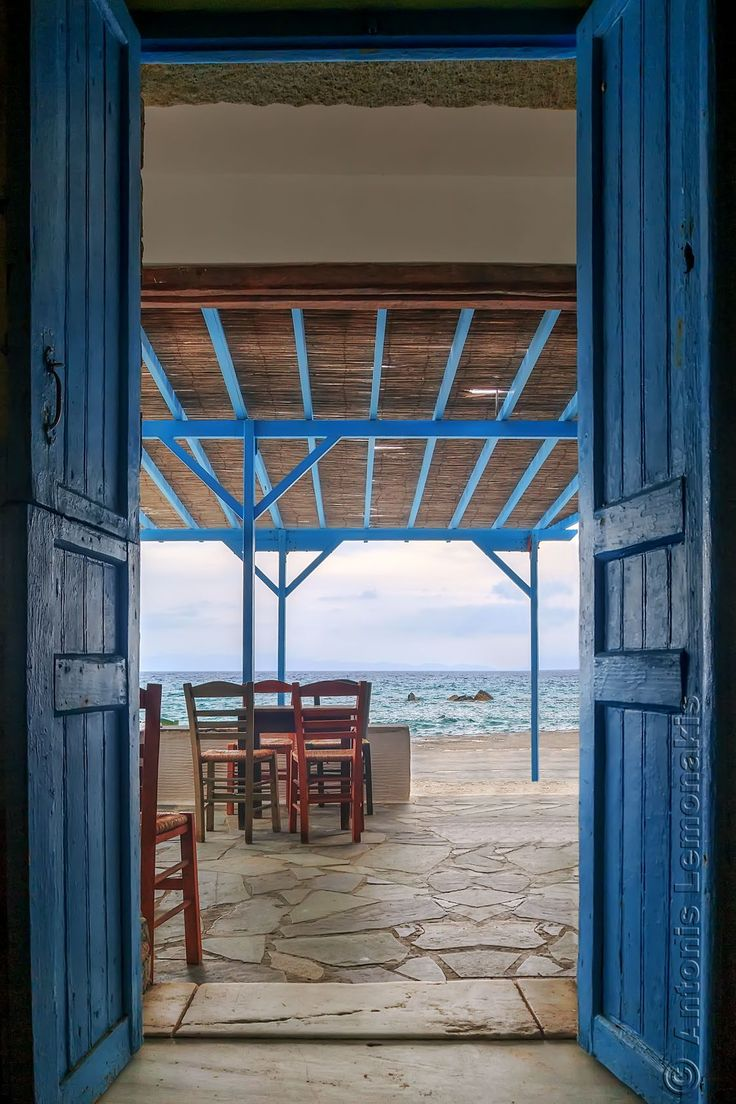 The entrance to a typical Greek tavern with blue doors, in front of the sea, in Tinos island, Greece