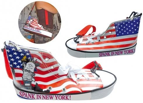 HELLO SPANK BORSA SCARPA NEW YORK  Borsa Free Time Hello Spank in tessuto a forma di scarpa con stampa della bandiera americana su un lato e sull'altro un disegno di Spank in vesti della statua delle Libertà e una scritta sulla gomma SPANK IS NEW YORK in entrambi i lati. Borsa a tracolla e chiusura a zip.