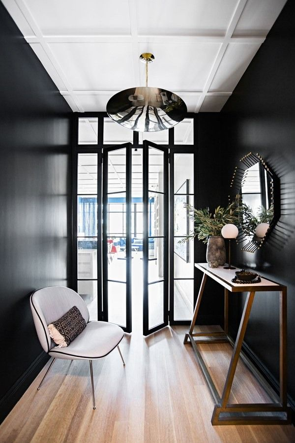 To reference the wall of windows in the living room, Brent installed iron-and-glass doors off the kitchen to create an intimate entry | archdigest.com