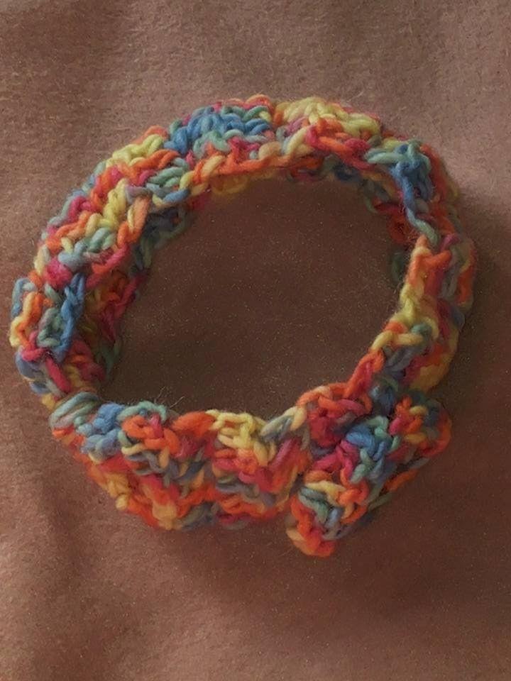 Copriorecchie in misto lana, lavorata ad uncinetto a mano libera, con guarnizione di fiorellino