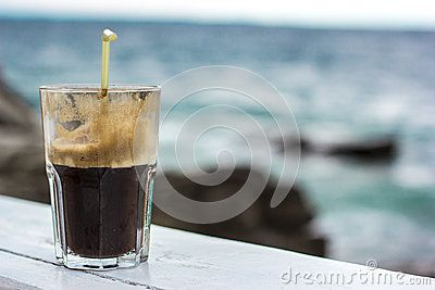 Coffee Frappe Fredo Iced in a glass with straw with sea background