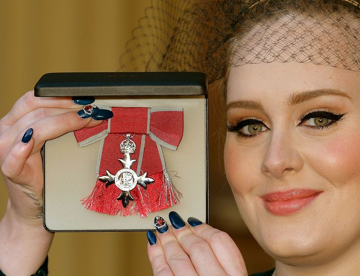 LONDON, ENGLAND - DECEMBER 19: Adele Adkins MBE holds her MBE award for services