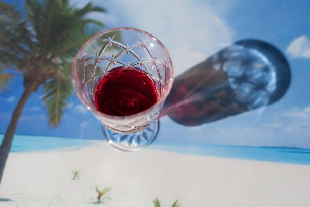 top view of red wine glass with tropical tablecloth background