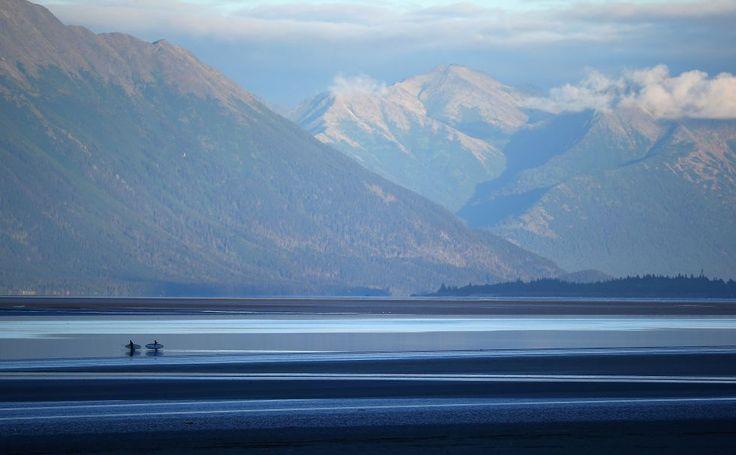 dos surferos esperan en las marismas de la ensenada de Cook a que llegue el 'Bore Tide' al brazo de Turnagain en Anchorage, Alaska. 14 de julio de 2014.El 'Bore Tide' es una fuerte marea que provoca olas de hasta 3 metros de altura, a una velocidad de 10-15 kilómetros por hora.