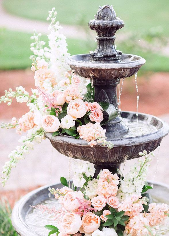 4. Floral fountain: If your venue has a fountain, floating florals are a must. We love a cascading look that drips down each tier of the water feature. #WeddingFlowers  #WeddingDecorations  #FlowerArrangements