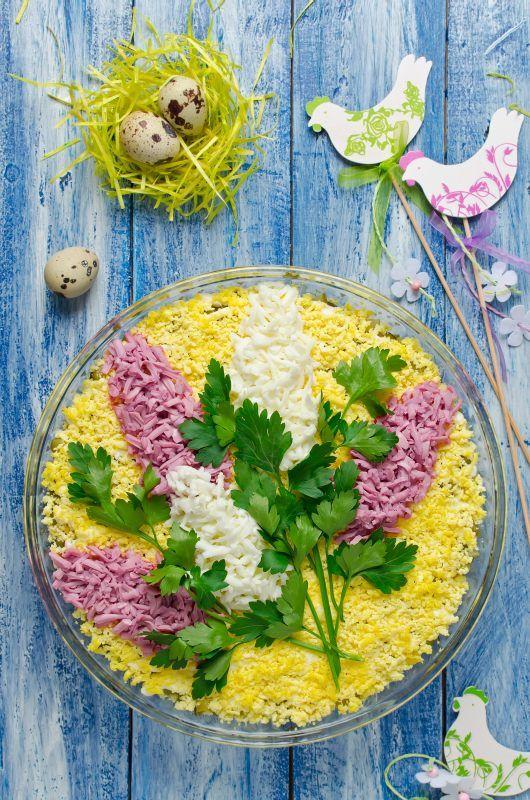 Składniki: 1 kg pieczarek, 3 łodygi selera naciowego, 4 jajka ugotowane na twardo, 1 puszka kukurydzy konserwowej,  sól, pieprz, 2 łyżki jogurtu typu greckiego, 4 łyżki majonezu. Do dekoracji: natka pietruszki lub koperek, posiekane białko i