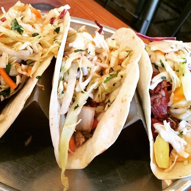 It's hard to see the meat, but trust us, it's there and it's delicious. Brisket, chicken, and pulled pork tacos from @thepigandpint in Fondren. #EatMississippi #EatFondren