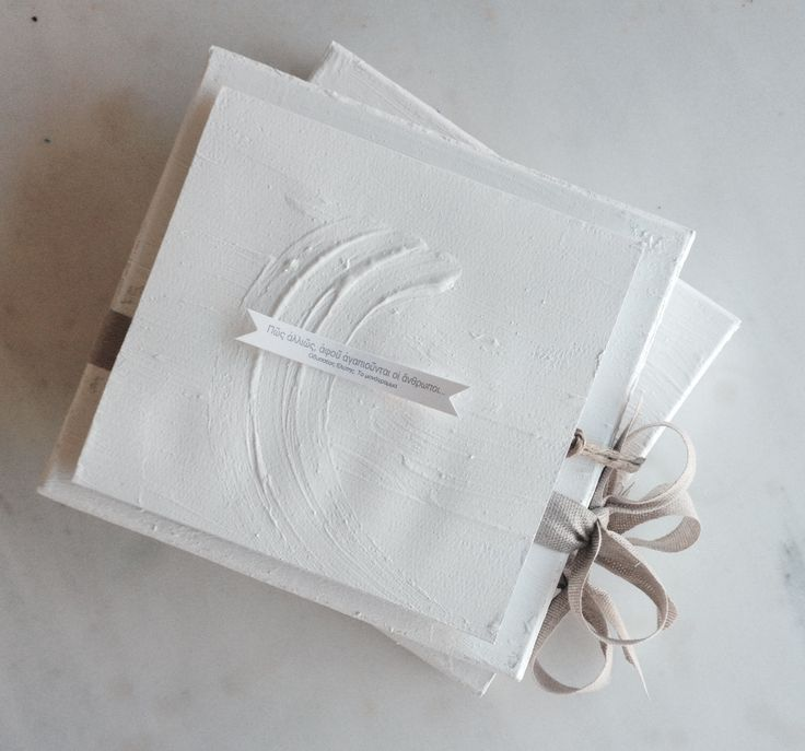 The perfect handcrafted wedding invitation for a memorable wedding in santorini | Total white with a a brush stroke ispired by the white water washed walls of the traditional houses on the Greek islands | www.bemyguest.com.gr