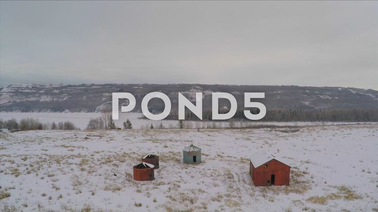 Aerial Shot Descend Over Frozen River Snow Field Abandoned Barn Ice Winter Drone - Stock Footage | by RyanJonesFilms